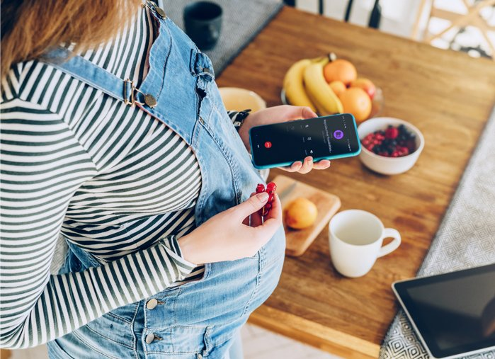 Pregnant surrogate mother checking mobile phone